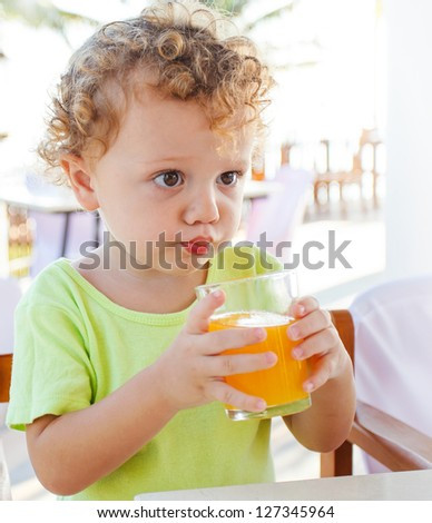 Cute boy drinking orange juice