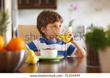 Cute boy drinking orange juice and eating muesli for breakfast