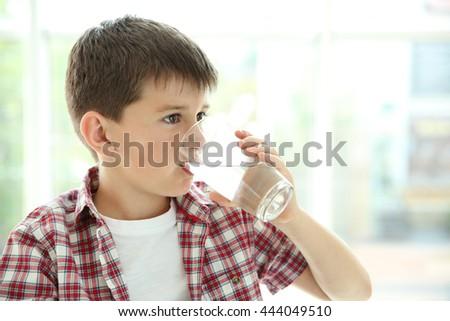 Cute boy drinking water on kitchen