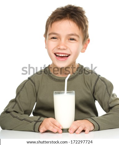 Cute boy drinks milk using a drinking straw, isolated over white