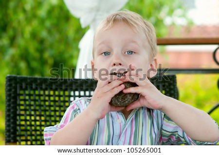 Cute boy eating  chocolate cake outdoors