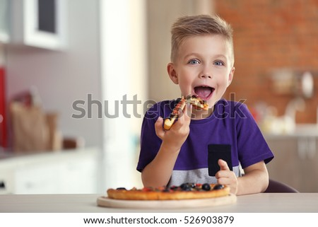 Cute boy eating pizza at home