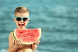 Cute boy eating watermelon on beach