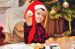 Cute boy eats sushi sitting under a Christmas tree in a red Santa hat and a red checkered shirt.