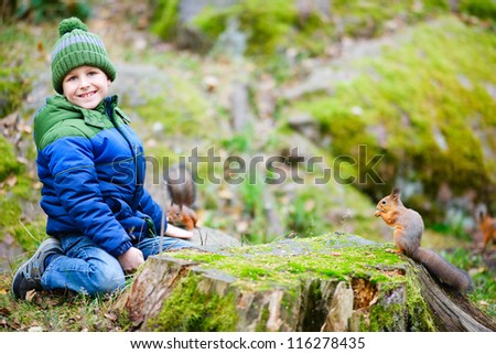 Cute boy feeding little squirrel at autumn park