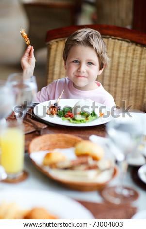Cute boy having delicious lunch in restaurant