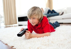 Cute boy holding a remote lying on the floor in the living-room