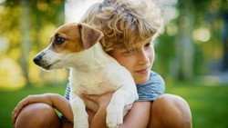 Cute Boy Holds His Favourite Pedigree Dog Friend while Having Picnic Outdoors on the Lawn. He Pets and Cuddles His Little Smooth Fox Terrier. Idyllic Summer House.