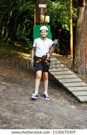 cute boy  in white t shirt in the adventure activity park with helmet and safety equipment. Young boy playing and having fun doing activities outdoors. Hobby, active lifestyle concept #1150670309