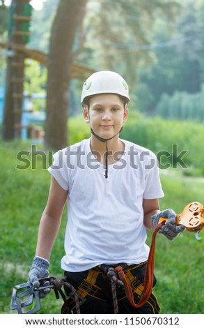 cute boy  in white t shirt in the adventure activity park with helmet and safety equipment. Young boy playing and having fun doing activities outdoors. Hobby, active lifestyle concept #1150670312