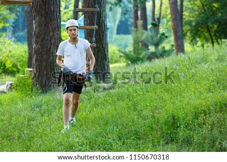 cute boy  in white t shirt in the adventure activity park with helmet and safety equipment. Young boy playing and having fun doing activities outdoors. Hobby, active lifestyle concept #1150670318