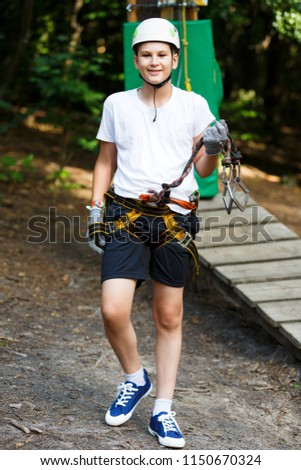 cute boy  in white t shirt in the adventure activity park with helmet and safety equipment. Young boy playing and having fun doing activities outdoors. Hobby, active lifestyle concept #1150670324