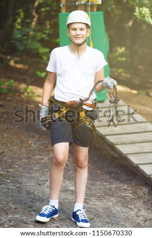 cute boy  in white t shirt in the adventure activity park with helmet and safety equipment. Young boy playing and having fun doing activities outdoors. Hobby, active lifestyle concept #1150670330
