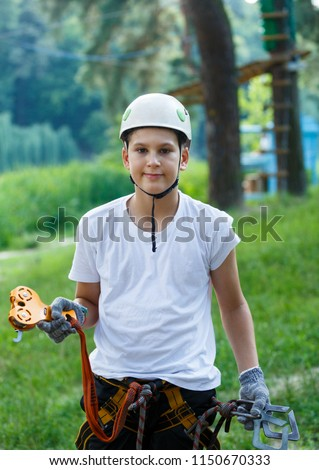 cute boy  in white t shirt in the adventure activity park with helmet and safety equipment. Young boy playing and having fun doing activities outdoors. Hobby, active lifestyle concept #1150670333