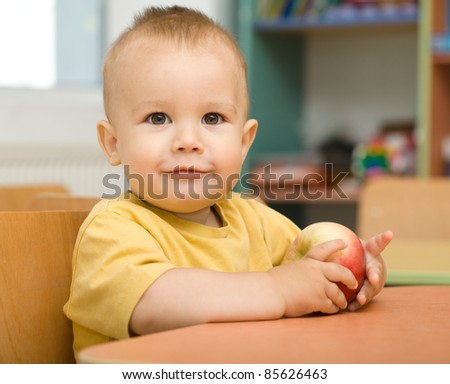 Cute boy is eating apple in preschool