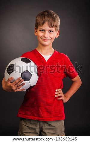 Cute boy is holding a football ball made of genuine leather  isolated on a black background. Soccer ball