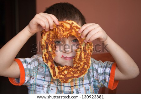 Cute boy is looking through the hole of pancake