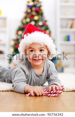 Cute boy laying in front of decorated Christmas tree