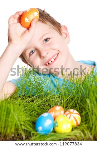 Cute boy looking for Easter eggs hidden in a grass