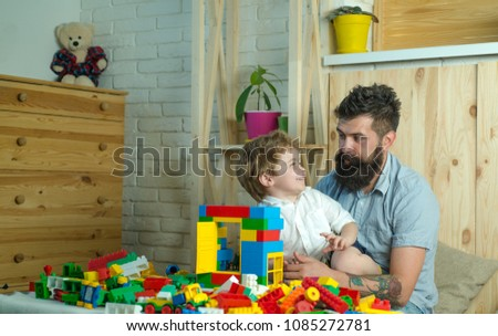 Cute boy looks at father. Handsome father and his cute son looking at each other and smiling while spending time together at home. Family and toys, happy beautiful child and bearded stylish father #1085272781