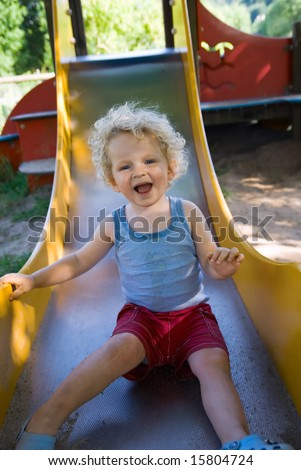 cute boy on a slide at the playground