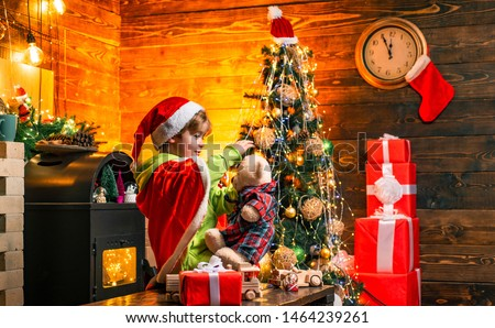 Cute boy play near christmas tree. Kid enjoy winter holiday at home. Home filled with joy and love. Make wish. Best wishes for you your family this christmas. Merry christmas and happy new year.