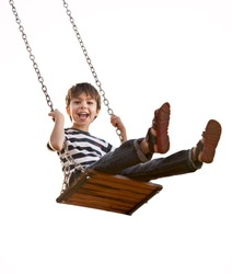 Cute boy playing on swing, having fun.  On a white background.
