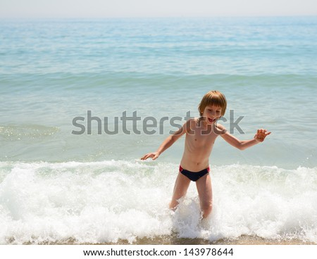 Cute boy playing on te bank of sea, summer vacation