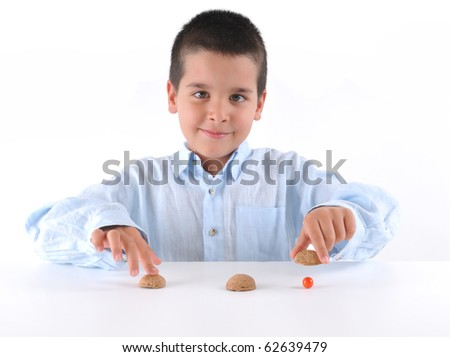 Cute boy playing traditional shell game with three walnut shells - a series of SHELL GAME images. - stock photo