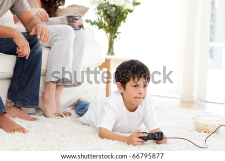 Cute boy playing video game lying on the floor at home with his parents