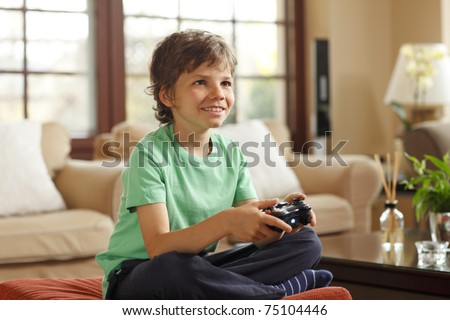 Cute boy playing video games at home