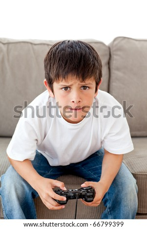 Cute boy playing video games sitting on the sofa at home