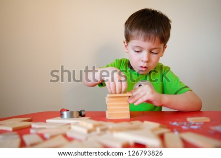 Cute boy playing with wooden kit