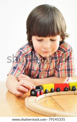 Cute boy playing with wooden train