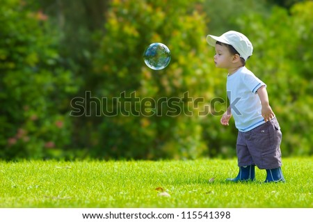 Cute boy plays with a giant bubble outside in the park