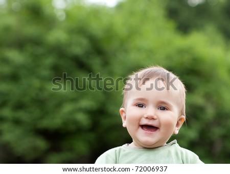 Cute boy portrait outdoor on blured green background