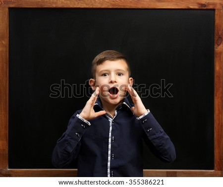 Cute boy posing at the clean blackboard, in the classroom #355386221
