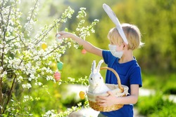 Cute boy protective face mask holding wicker basket with white toy rabbit during hunt for easter eggs in spring park on Easter day.Traditional easter festival outdoors during coronavirus pandemic