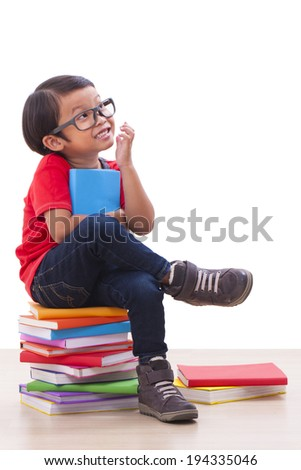 Cute boy reading a book while sitting on books