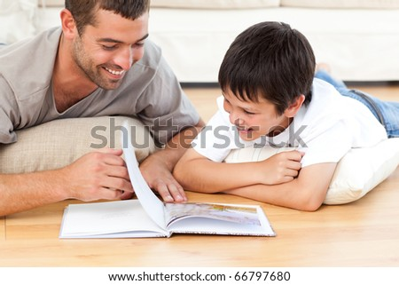 Cute boy reading a book with his father on the floor at home