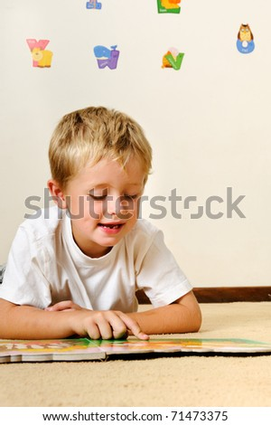 cute boy reads book on the floor at school