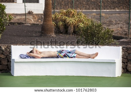 cute boy relaxing on a bench in the pool area