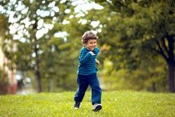 Cute boy running across grass und smiling.