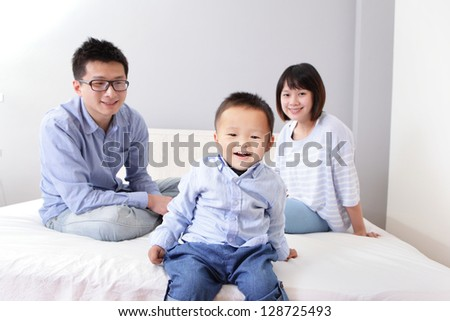 cute boy sitting on bed and happy father, mother look at he, asian family at home with gray wall for copy space