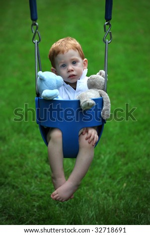 Cute boy sitting on swing with soft toys