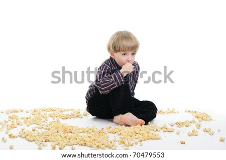 cute boy sitting on the floor, surrounded by lots of popcorn spreaded across the floor