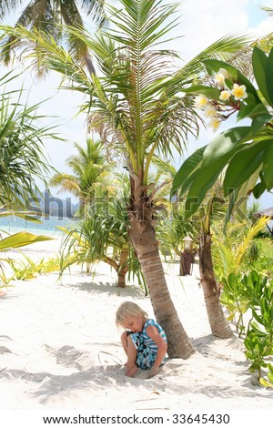 Cute boy sitting on the white sand of tropical paradise
