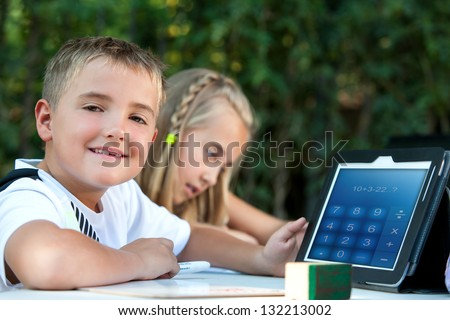 Cute boy student showing maths homework on tablet outdoors.