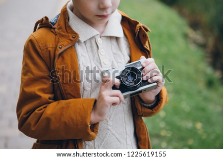 Cute boy walks and poses in a colorful autumn Park. The boy takes pictures on the camera. Toning.