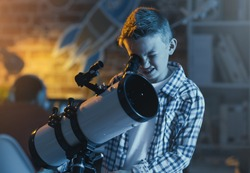 Cute boy watching stars through a telescope at night in his bedroom, imagination and discovery concept